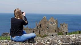 Den unga kvinnan tar foto av den Dunluce slotten i norr Irland arkivfilmer