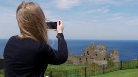 Den unga kvinnan tar foto av den Dunluce slotten i norr Irland lager videofilmer