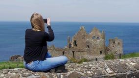 Den unga kvinnan tar foto av den Dunluce slotten i norr Irland stock video