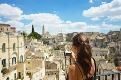 Den unga kvinnan tar fotoet med den mirrorless kameran till den gamla staden av Matera Härligt handelsresandeflickabesök Sassi di royaltyfri bild