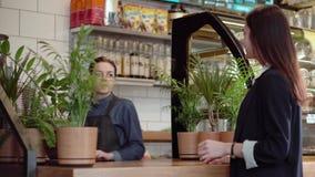 Den unga kvinnan tar kaffe från en baristaflicka lager videofilmer
