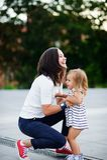 Den unga kvinnan tar den lilla dottern på händer Royaltyfri Fotografi