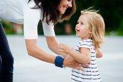 Den unga kvinnan tar den lilla dottern på händer Arkivfoto
