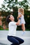 Den unga kvinnan tar den lilla dottern på händer Arkivbild