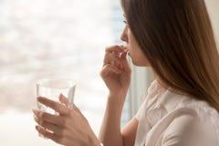 Den unga kvinnan tar preventivpilleren med exponeringsglas av vatten i hand arkivbild