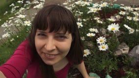 Den unga kvinnan tar selfie, medan sitta på blommande tusenskönor lager videofilmer