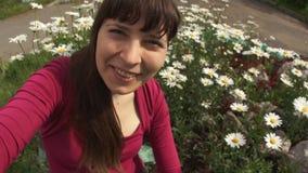 Den unga kvinnan tar selfie, medan sitta på blommande tusenskönor stock video