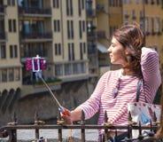 Den unga kvinnan tar selfies på den Ponte Vecchio bron i Florence - FLORENCE/ITALIEN - SEPTEMBER 12, 2017 Royaltyfri Bild