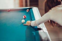 Den unga kvinnan tar snookerskottet royaltyfri fotografi