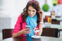 Den unga kvinnan äter efterrätten och samtal på telefonen Arkivfoto