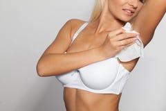 Den unga kvinnan torkar armhålan med våta wipes Arkivbilder