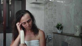 Den unga kvinnan torkar hennes hår med en hårtork St?ende som skjutas i spegelreflexion arkivfilmer