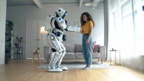 Den unga kvinnan trycker på en cyborg i en vardagsrum arkivfilmer