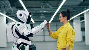 Den unga kvinnan trycker på högväxta robotens hand stock video