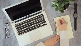 Den unga kvinnan trycker på touchpaden av bärbara datorn och skriver i anteckningsbok inomhus stock video