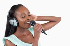 Den unga kvinnan tycker om att sjunga royaltyfria foton