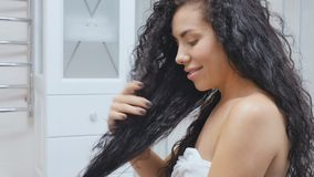 Den unga kvinnan tycker om en friskhet av hennes lockiga hår arkivfilmer