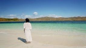 Den unga kvinnan tycker om Labuan Bajo strandsikt arkivbilder