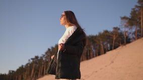 Den unga kvinnan tycker om solnedgång under guld- timme på en flodstrand i bärande vitt flåsanden, sweatshort och omslag för vår  stock video