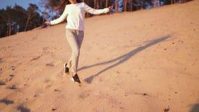 Den unga kvinnan tycker om solnedg?ng i ultrarapid under guld- timme p? dyn f?r sand f?r flodstrand en vit, i att b?ra f?r v?r so stock video
