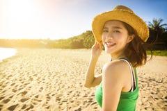 Den unga kvinnan tycker om sommarsemester på stranden arkivfoto