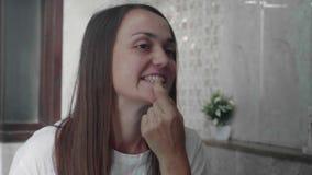 Den unga kvinnan undersöker hennes tänder framme av spegeln stock video