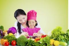Den unga kvinnan undervisar hennes dotter att laga mat Arkivfoton