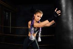 Den unga kvinnan utbildar i boxningsring med den tunga stansa påsen royaltyfri fotografi
