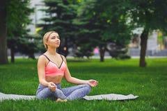 Den unga kvinnan utomhus, kopplar av meditation poserar Arkivbild