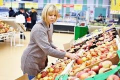 Den unga kvinnan väljer äpplen Royaltyfria Bilder