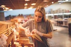 Den unga kvinnan väljer bröd i lagret Royaltyfri Bild