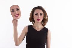 Den unga kvinnan väljer en maskering Arkivfoto