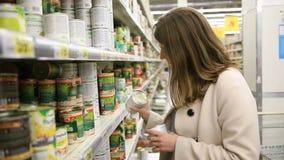 Den unga kvinnan väljer på burk mat i lagret arkivfilmer