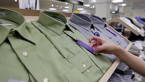 Den unga kvinnan väljer skjortan för hennes make lager videofilmer