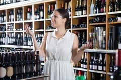 Den unga kvinnan väljer vin i avdelning av supermarke Royaltyfria Foton