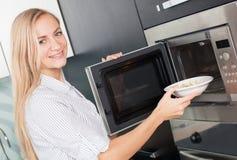 Den unga kvinnan värmer mat i mikrovågen upp royaltyfria foton