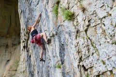Den unga kvinnan vaggar klättrareklättring i grotta royaltyfri fotografi