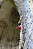 Den unga kvinnan vaggar klättrareklättring i grotta royaltyfria foton