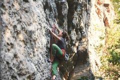 Den unga kvinnan vaggar klättrareklättring på klippan Royaltyfri Bild