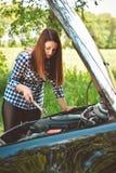 Den unga kvinnan vid vägrenen efter hennes bil har bruten down tonad bild Arkivfoto