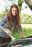 Den unga kvinnan vid vägrenen efter hennes bil har bruten down tonad bild Royaltyfria Bilder