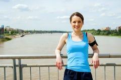Den unga kvinnan vilar efter körningen som joggar passformen i staden Arkivbild