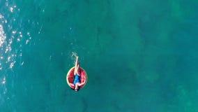 Den unga kvinnan vilar på en gummicirkel som svävar i havet stock video