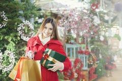 Den unga kvinnan visar att hennes gåvapackar inom jul shoppar Royaltyfri Fotografi