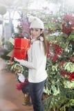 Den unga kvinnan visar att hennes gåvapackar inom jul shoppar Royaltyfri Foto