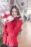 Den unga kvinnan visar att hennes gåvapackar inom jul shoppar Fotografering för Bildbyråer