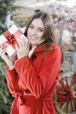 Den unga kvinnan visar att hennes gåvapackar inom jul shoppar Arkivfoto