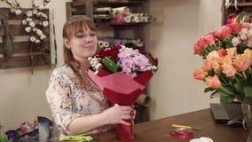 Den unga kvinnan visar en bukett som hon samlade i en blomsterhandel lager videofilmer