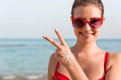 Den unga kvinnan visar fredgest och har solform på hennes hand på stranden royaltyfri fotografi