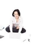 Den unga kvinnliga arbetaren som använder bärbara datorn i lotusblomma, poserar på den vita backgrouen Arkivfoto